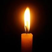 lit candle against black background